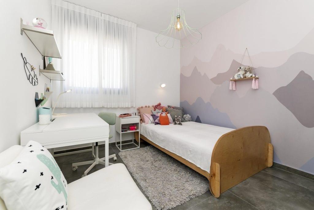 מיטה בסגנון נורדי שעוצבה במיוחד לחדר השינה של הילדה. המיטה עשויה מבירץ'. על הקיר הודבק טפט בצבעי פסטל ורודים, סגולים ואפורים. הריהוט בצבע מנטה מתאים לנגרות בחדר. עיצוב פנים ותאורה - שרי בר-נע גבעון