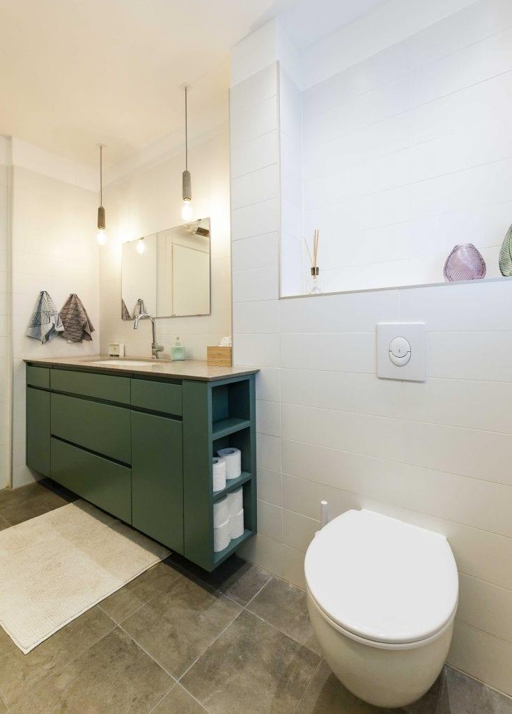 ארון האמבטיה תוכנן כך שיהיה דו חזיתי, ובצידו ישנן נישות לאחסון נייר טואלט. עיצוב פנים ותאורה - שרי בר-נע גבעון