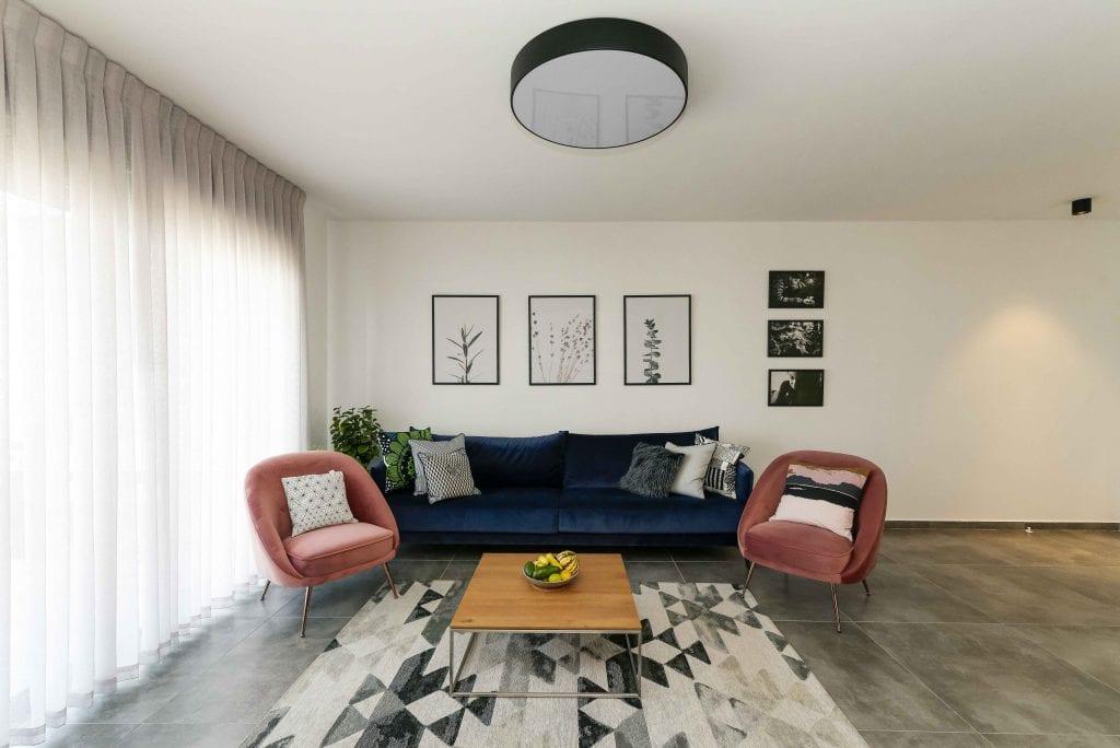 ספת קטיפה כחולה וכורסאות קטיפה ורודות עם שטיח גיאומטרי בשחור-לבן. עיצוב פנים ותאורה - שרי בר-נע גבעון