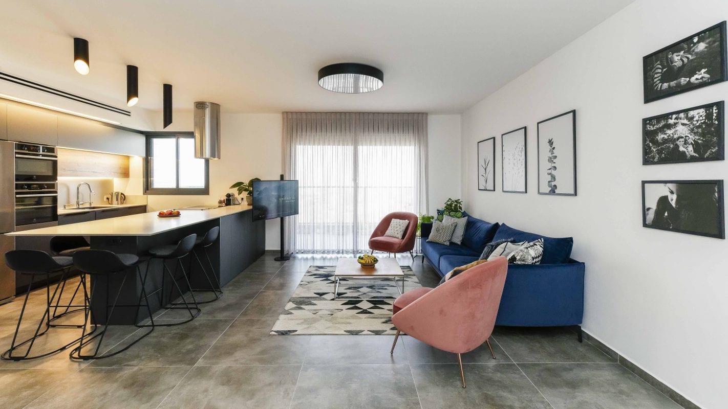 סלון ומטבח בחלל המשותף המשלב בין כחול ורוד, האי משמש כפינת אוכל. עיצוב פנים ותאורה - שרי בר-נע גבעון