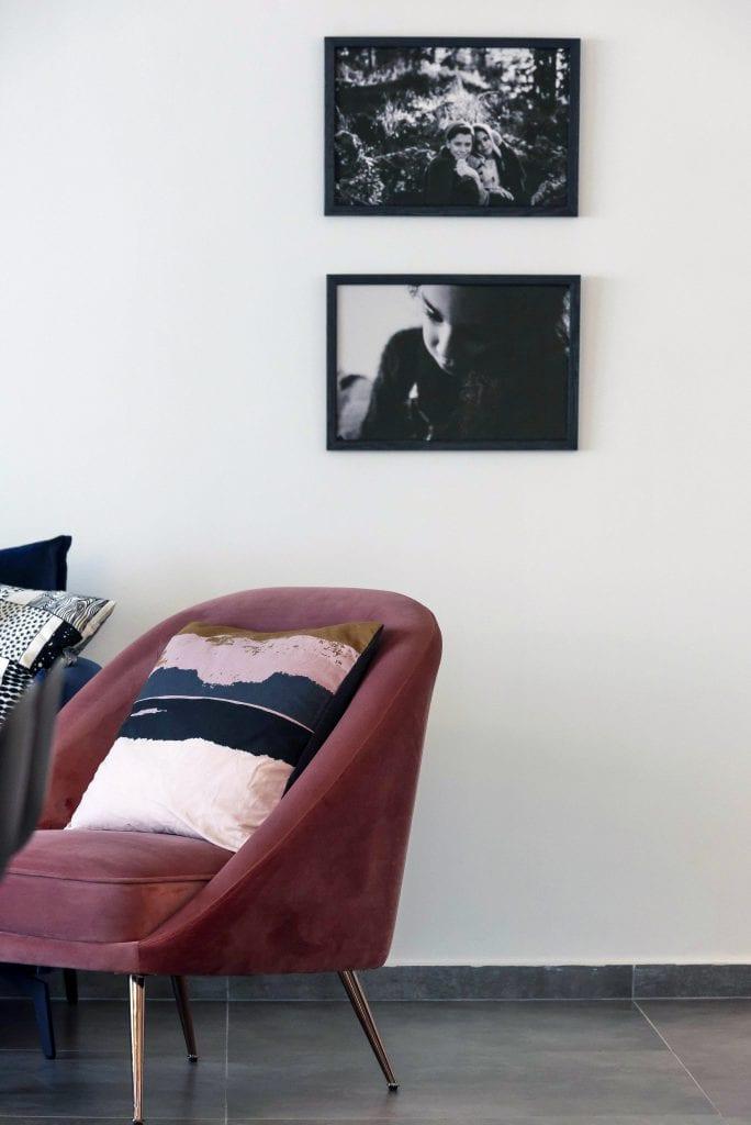 כורסה ורודה מקטיפה, על הקיר תלויות תמונות משפחתיות בשחור-לבן שצילם הלקוח. עיצוב פנים ותאורה - שרי בר-נע גבעון