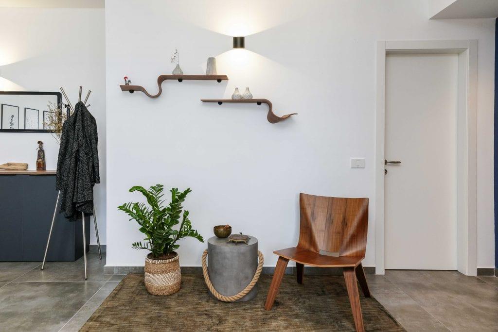 מבואת הכניסה לבית ובה כורסאת עץ, מדפים דקורטיביים של סטודיו cozy ופריטים קטנים שנבחרו בתשומת לב רבה. עיצוב פנים ותאורה - שרי בר-נע גבעון