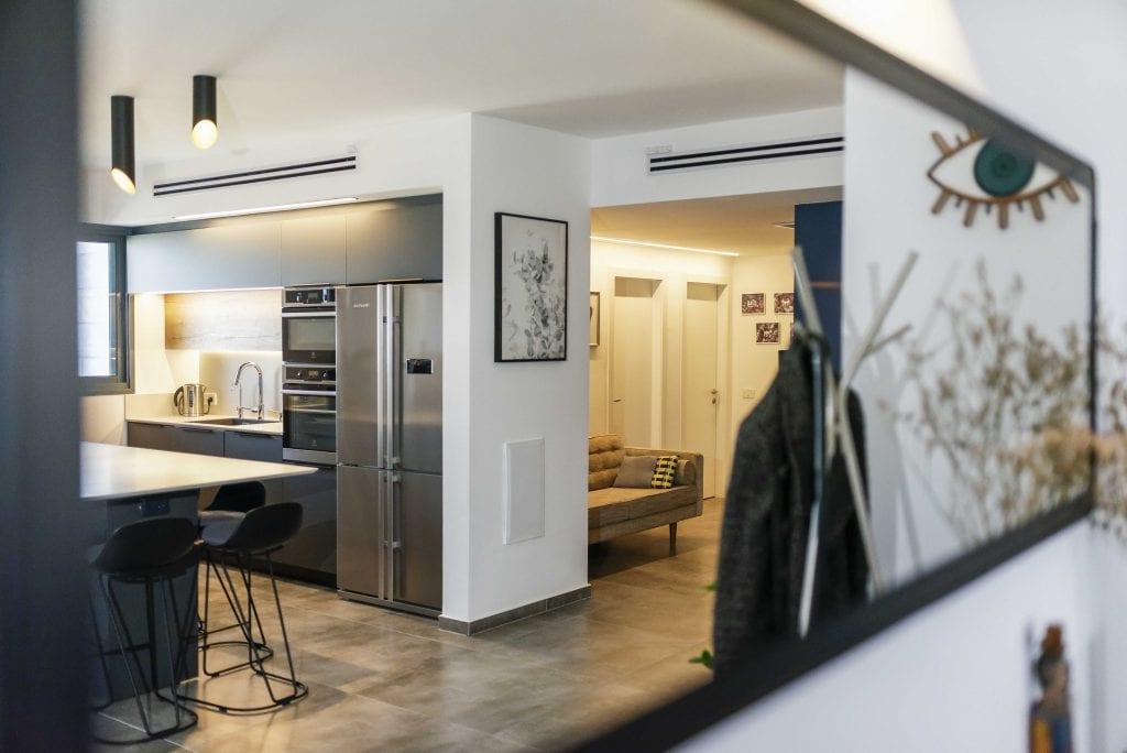 הסלון משתקף במראה הממוקמת בכניסה לבית ותורמת לתחושת מרחב בחלל הציבורי. עיצוב פנים ותאורה - שרי בר-נע גבעון