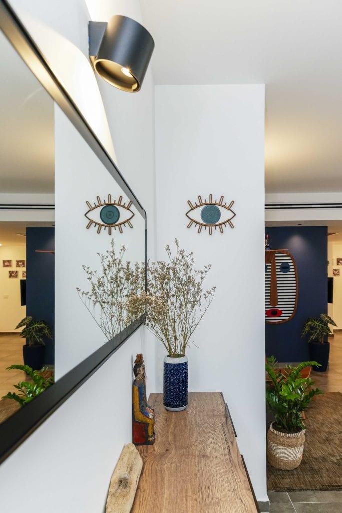 המזנון בכניסה לבית משמש להצגת חפצי נוי וכמקום אחסון לשמירה על כניסה מסודרת לבית. עיצוב פנים ותאורה - שרי בר-נע גבעון