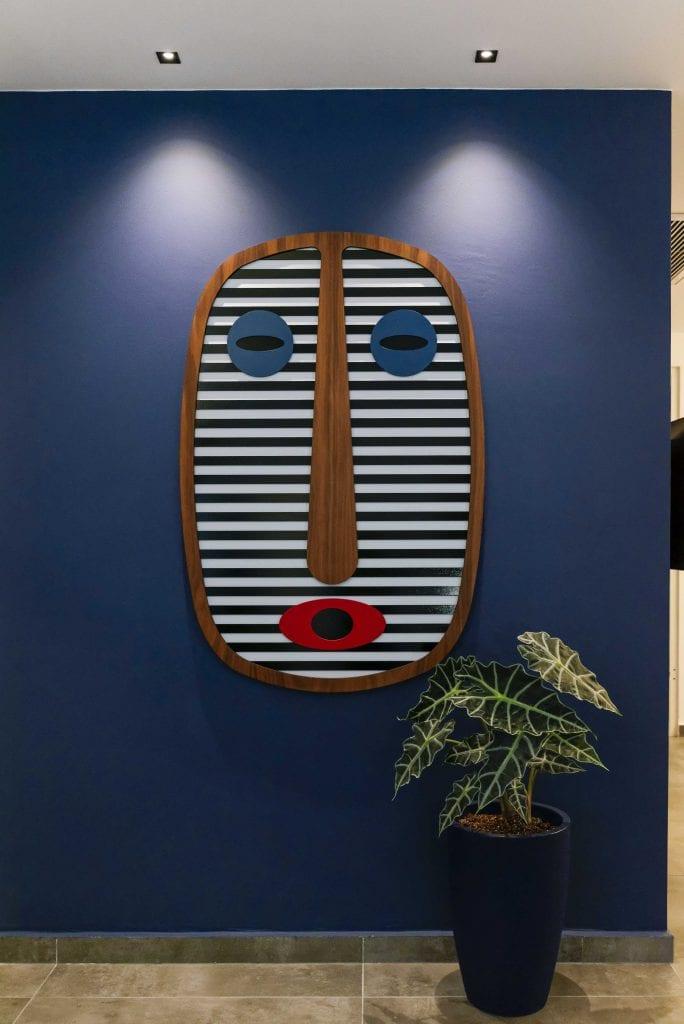 מסכה של Umasqu, על רקע קיר המסדרון הכחול. התאורה עוצבה במיוחד להארת המסכה והדגשת הצבעים הכחולים. עיצוב פנים ותאורה - שרי בר-נע גבעון