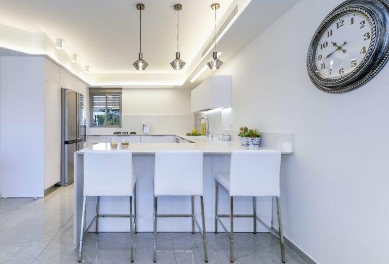 הדלפק הלבן במטבח משמש כפינת אוכל יומיומית, עם כיסאות בר לבנים, וכמשטח עבודה, ומגדיל את מקומות האחסון של המטבח. עיצוב פנים ותאורה - שרי בר-נע גבעון