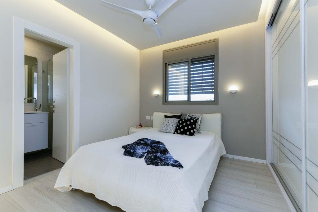 הפלטה הלבנה-אפורה נשמרה גם לחדר השינה של ההורים, ליצירת תחושה מרגיעה וחמה. נבחרו מנורות קריאה המשלבות תאורת אווירה ותאורת קריאה. עיצוב פנים ותאורה - שרי בר-נע גבעון