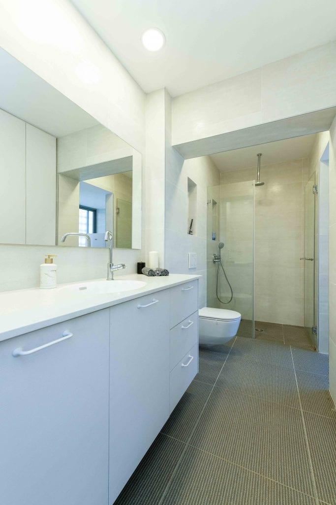 חדר הרחצה הלבן ממשיך עם בחירת הצבע הלבן גם בחיפויים. עיצוב פנים ותאורה - שרי בר-נע גבעון