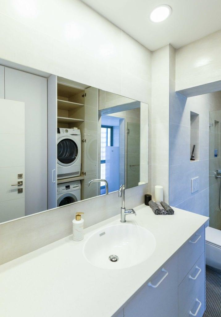 חדר הרחצה הכללי אוחד עם חדר הכביסה. מכונת הכביסה והמייבש מוסתרים בארון. האמבט בוטל והוחלף במקלחון. עיצוב פנים ותאורה - שרי בר-נע גבעון