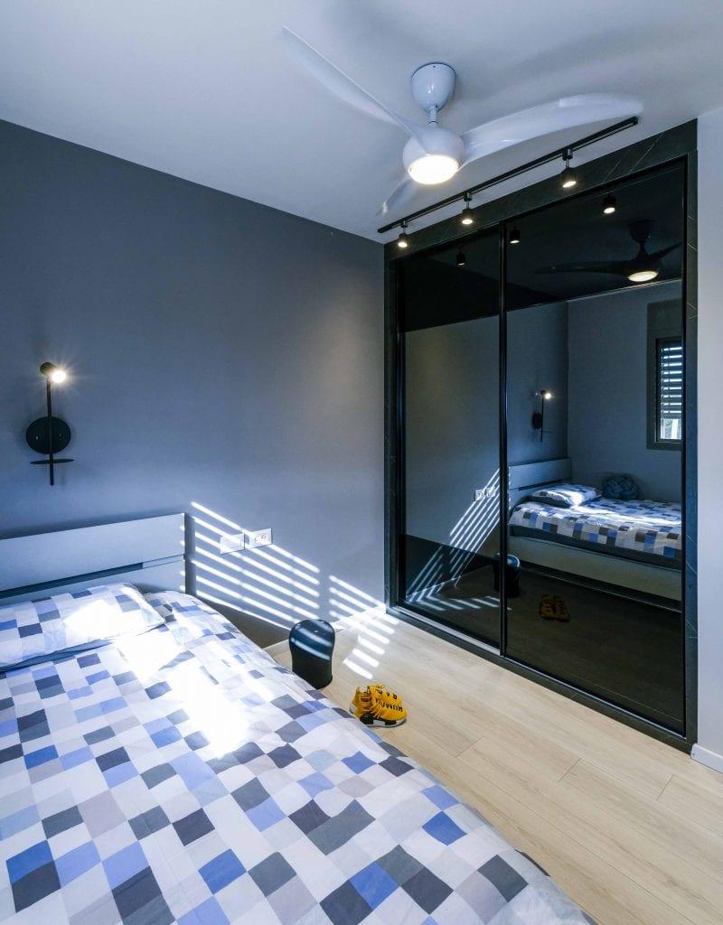 חדר שינה לנער מתבגר, השונה בעיצובו משאר הדירה, ובו נבחרו שני גוונים של אפור כהה עם ארון בגימור מראה המתאים לנער מתבגר. עיצוב פנים ותאורה - שרי בר-נע גבעון