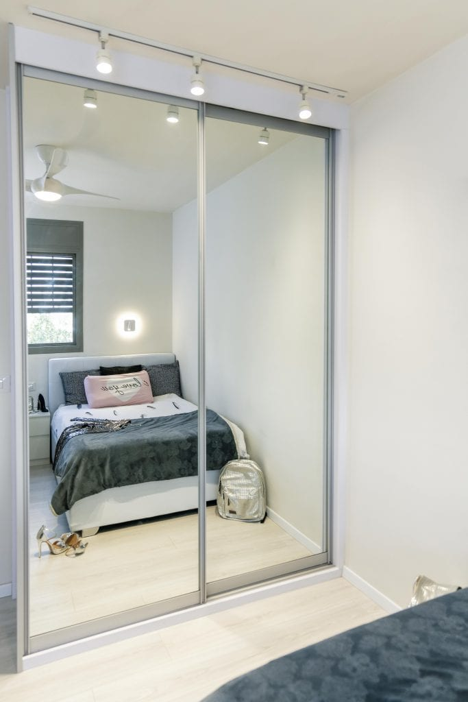 הארון הגדול בגימור מראה, ומעליו תאורה עילית, בחדר השינה של הבחורה הצעירה