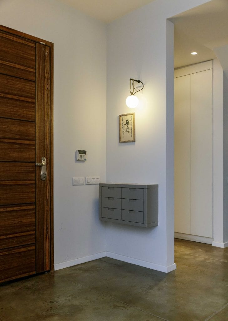 גוף תאורה צמוד קיר בעיצוב Neri & Hu לחברת Artemide המאיר את מבואת הכניסה לבית. תכנון ועיצוב תאורה - שרי בר-נע גבעון