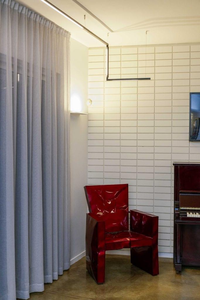 סוף פס התאורה מסתובב לכיוון הפסנתר ומאיר על הפסנתר ועל הכורסה האדומה בפינת הקריאה. תכנון ועיצוב תאורה - שרי בר-נע גבעון