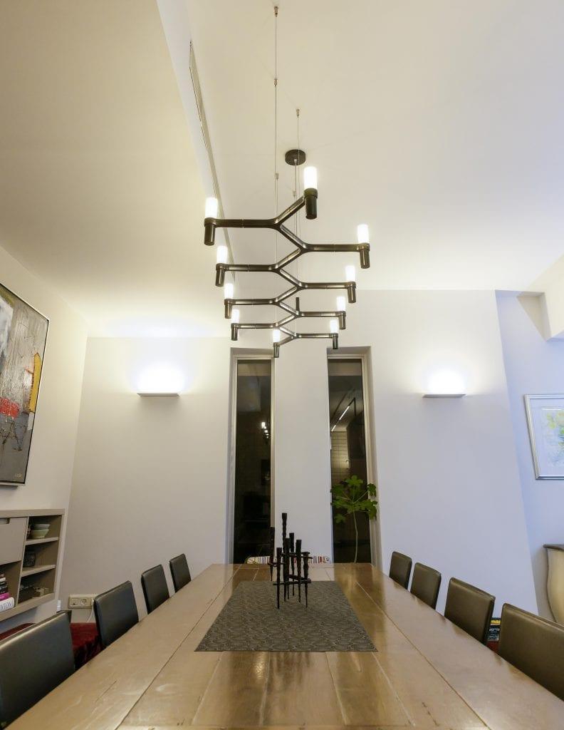 גוף התאורה Crown Plana Linea, בעיצוב מודרני דמוי שנדליר, של חברת Nemo Lighting מאיר את שולחן פינת האוכל ומשתלב עם העיצוב המודרני של החלל ורגלי הברזל השחורות של שולחן האוכל. תכנון ועיצוב תאורה - שרי בר-נע גבעון