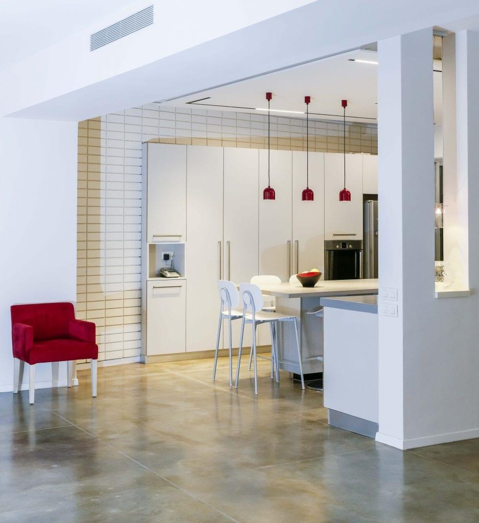 מבט מכיוון פינת האוכל. בנישה גוף תאורה דקורטיבי תלוי אליו הותאמו גופי התאורה התלויים מעל הדלפק במטבח. תכנון ועיצוב תאורה - שרי בר-נע גבעון