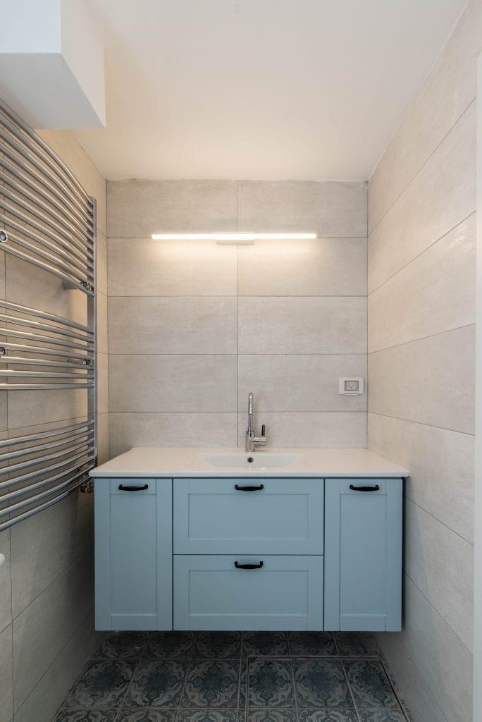 ארון האמבטיה, הכיור והמראה בחדר הרחצה של יחידת הדיור. עיצוב פנים ותאורה - שרי בר-נע גבעון